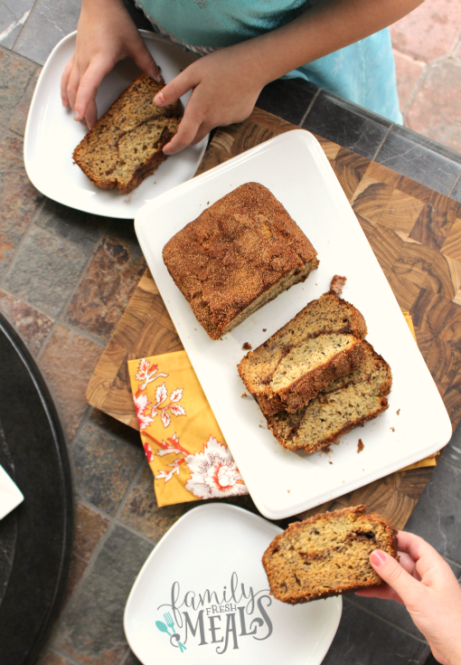 Cinnamon Swirl Banana Bread slices on a plate, with people taking a slice