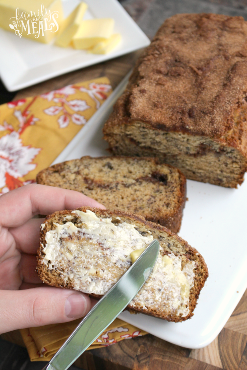 Spreading butter on a slice of Cinnamon Swirl Banana Bread