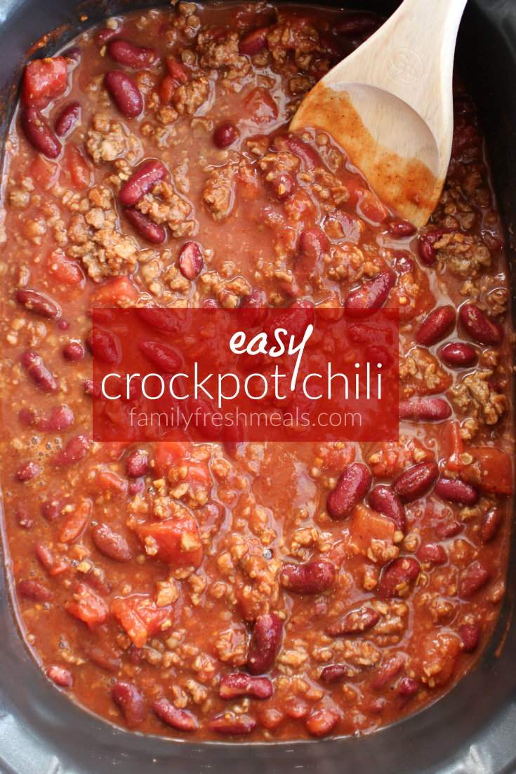 Easy Crockpot Chili in a slow cooker with a wooden spoon