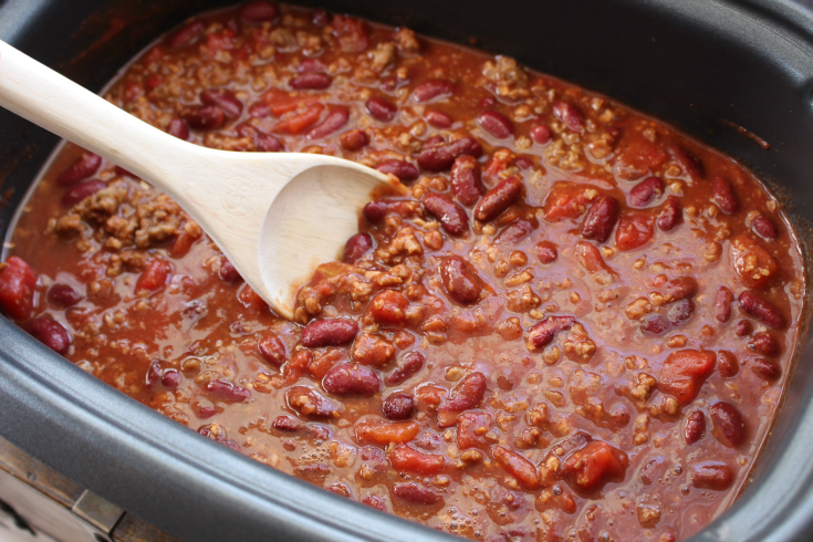 Easy Crockpot Chili - Chili in a crockpot and a wooden spoon stirring
