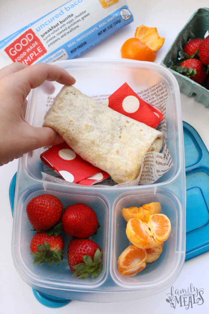 Breakfast burrito and fruit packed in a plastic lunchbox