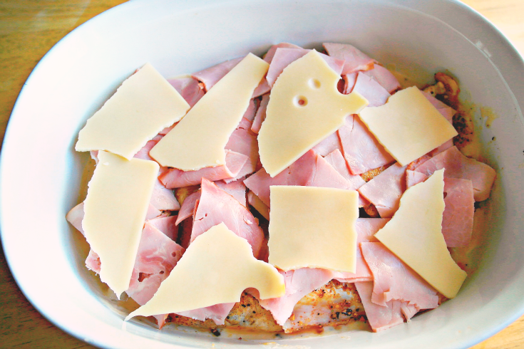 ham and sliced cheese added to the top of chicken
