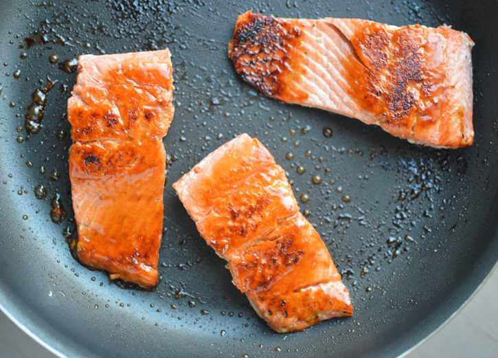 Easy Honey Glazed Salmon - salmon filets cooking in a pan