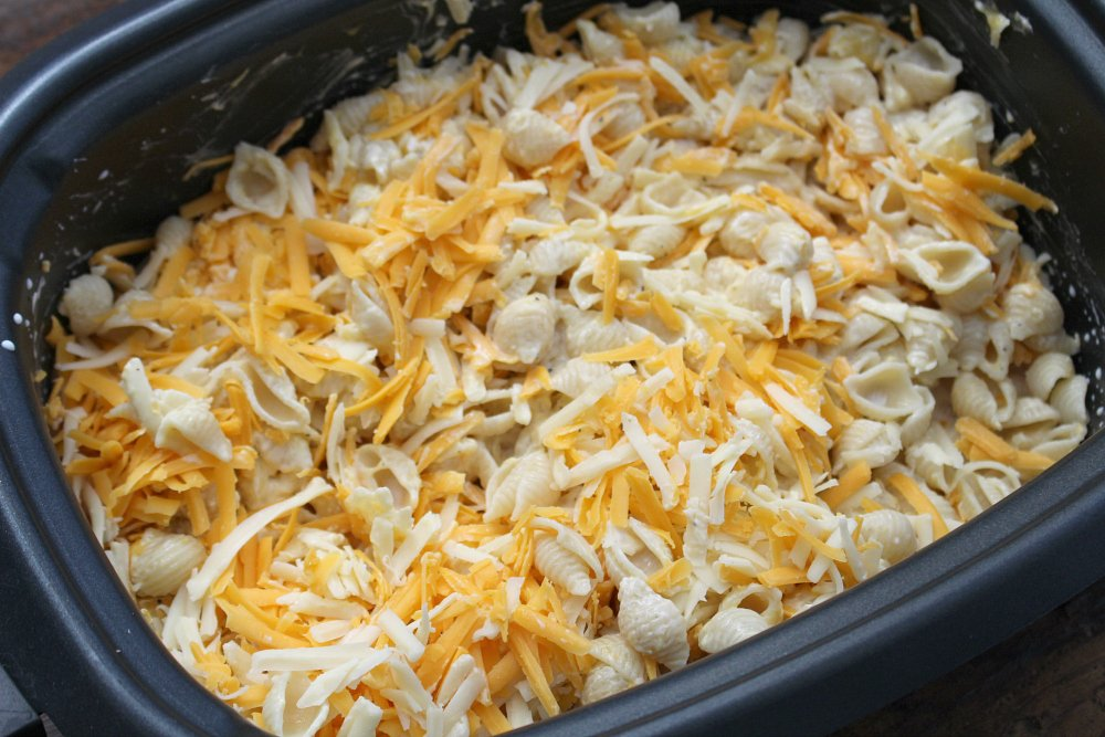 The Best Creamy Crockpot Mac and Cheese - shredded cheeses add to noodle mixture