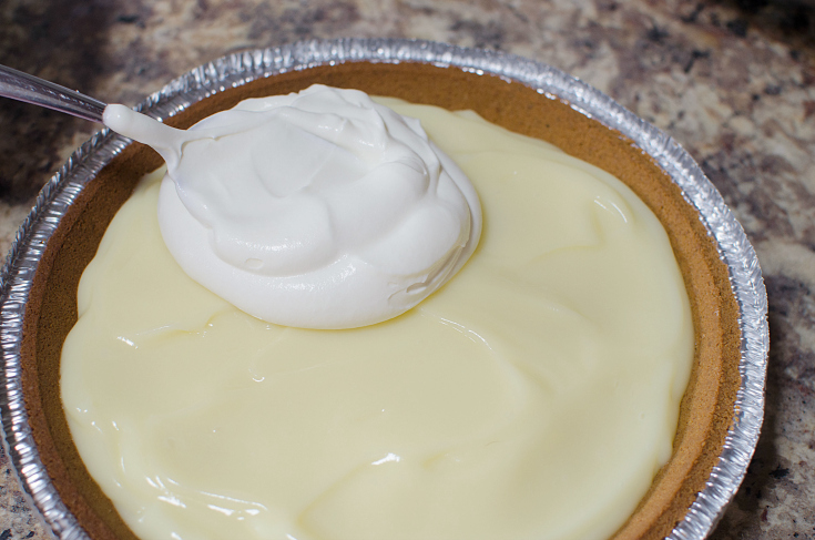 Grandma's Banana Cream Pie - Placing whipped cream on top of pie