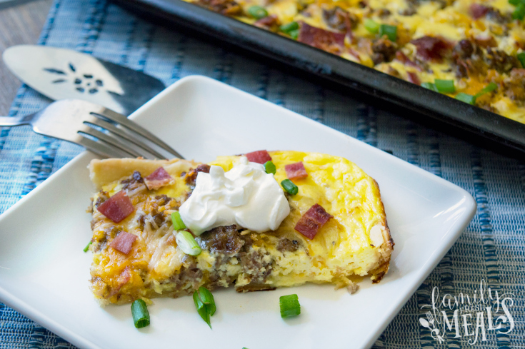 Meat Lovers Breakfast Bake Slab - Slice of breakfast bake on a white plate, topped with sour cream