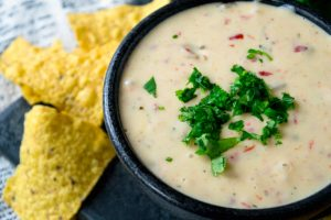 Crockpot White Queso Dip - Dip served in a dip bowl, topped with chilantro