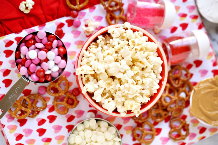 Valentines' Snack Mix with Free Printables - Ingredients of popcorn, pretzels m&m's white chocolate and peanut butter