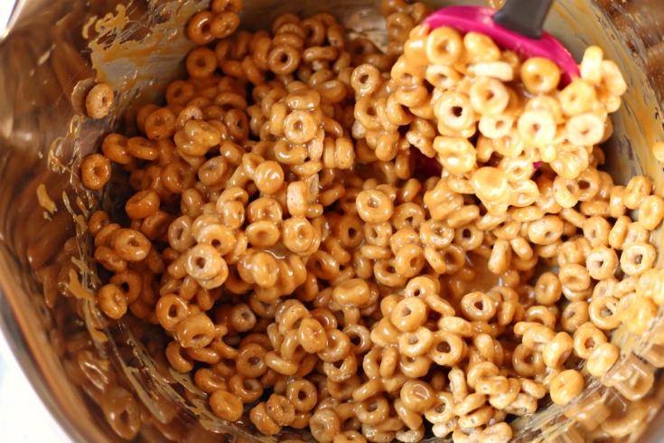 No Bake Chocolate Caramel Cereal Bars - Mixing together cheerios and caramel