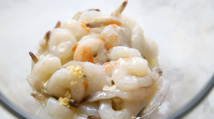 Crockpot Cheesy Grits and Shrimp - Raw shrimp in a bowl with butter, garlic and hot sauce