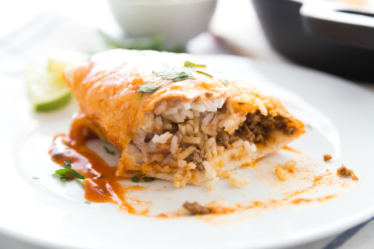One Pan Smothered Beef Skillet Recipe - Burrito cut in half on a white plate