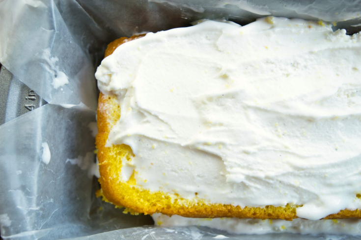 Easy Lemon Ice Cream Cake - Sliced cake in bread pan with ice cream spread on top