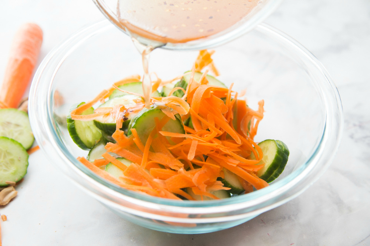 Thai Cucumber Salad - cucumber slices, carrot shreds, in a glass bowl with sauce