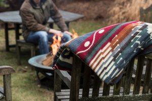 Ecuadane Ecuador Blanket draped over a wooden chair by a campfire