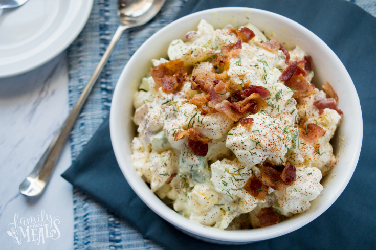 Cauliflower Potato Salad served in a white bowl and topped with bacon