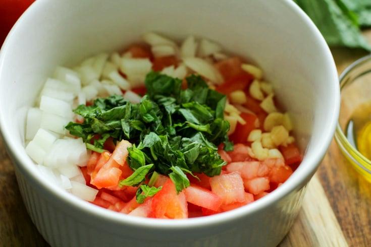 Easy Fresh Bruschetta Recipe - Chopped tomatoes, onion, garlic and basil in a white bowl