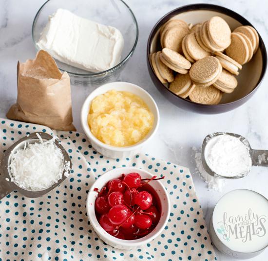 Pina Colada Lush Cake - Ingredients on a marble counter- cherries, vanilla oreos, milk, powdered sugar, cream cheese, pineapple, coconut, jello mix