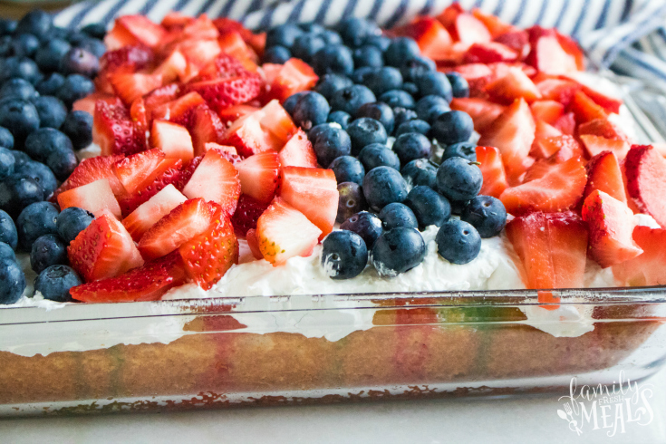 Red White and Blue Poke Cake - Fresh strawberry and blueberries placed on top of a white cake, in a glass baking dish
