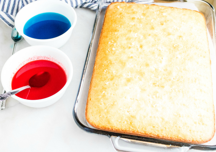 Red White and Blue Poke Cake - White cake baked in a glass baking dish. Two white bowls with red and blue liquid