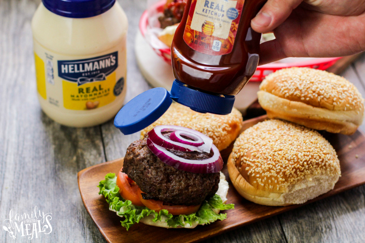 The Best Burgers Recipe - Served on a bun with tomato, lettuce, onion and ketchup