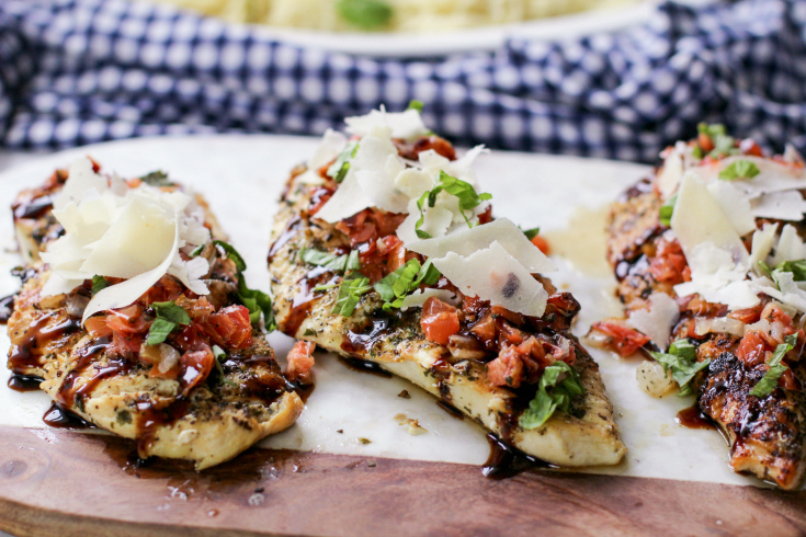 Bruschetta Chicken - Chicken breast on cutting board, topped with bruschetta, parmesan cheese and parsley - Family Fresh Meals