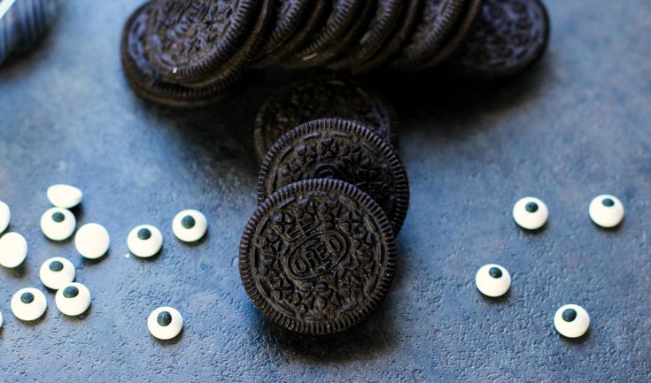 Spooky Halloween Oreos - Oreo cookies and candy eyeballs on a baking sheet