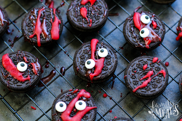 Spooky Halloween Oreos - Oreo cookies layed out on a drying rack with red frosting splattered and candy eyes