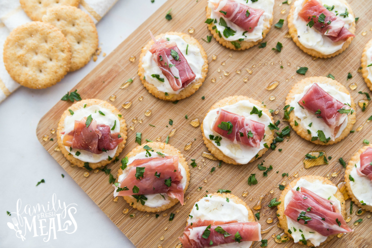 Easy Creamy Prosciutto Cracker Appetizer - Appetizers on a cutting board, drizzled with honey and parsly