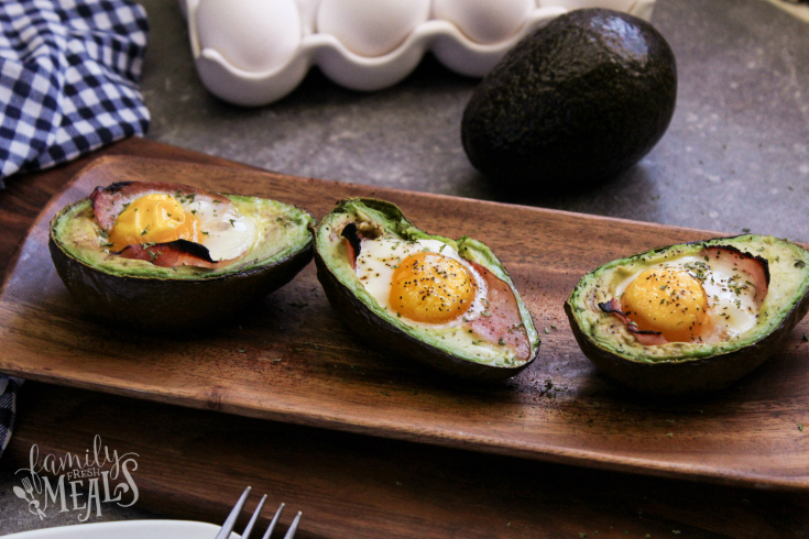 Avocado Egg Bake - Baked avocadoes on a wooden serving dish - Breakfast Avocados