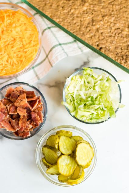 Bacon Cheeseburger Dip - Topping ingredients in small bowls_ bacon, pickles, shredded lettuce and shredded cheese