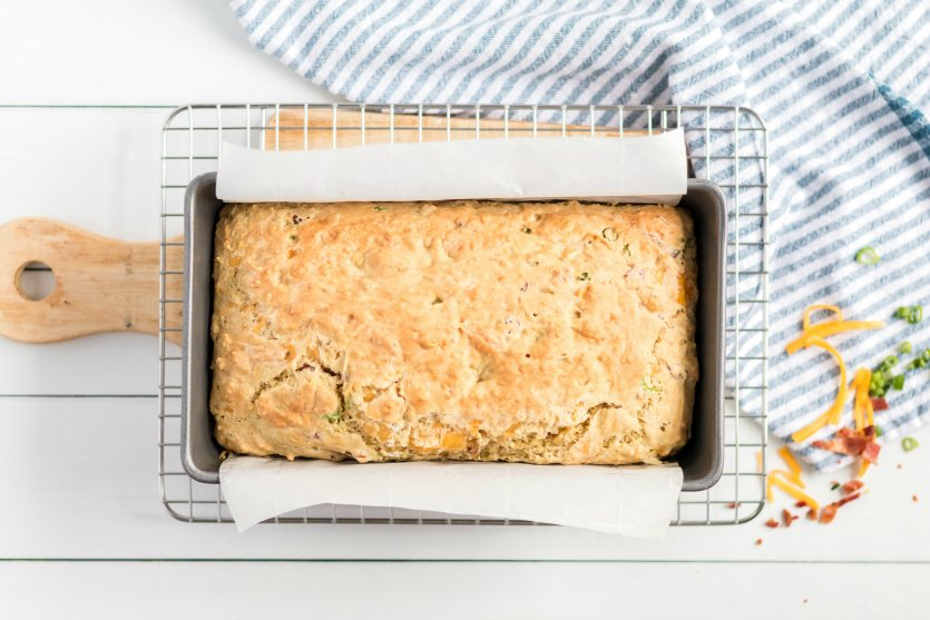 Bacon Cheddar Irish Soda Bread - Baked bread in a loaf pan cooling on wire rack