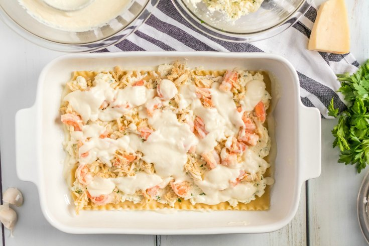 Easy Seafood Lasagna - Creamy sauce placed over seafood - Family Fresh Meals