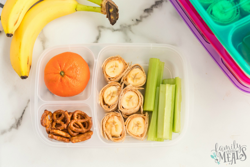 Banana Roll Up Lunch Box Idea - Packed in Easy Lunchboxes with celery, orange and pretzels - Family Fresh Meals