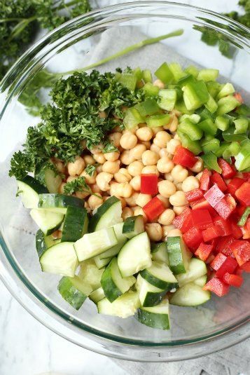 Cucumber Chickpea Salad - vegetables, beans and seasoning in glass bowl - Family Fresh Meals