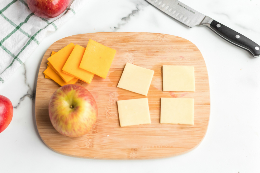 DIY Cheese and Crackers Lunchables - cheese slices on a cutting board - Family Fresh Meals