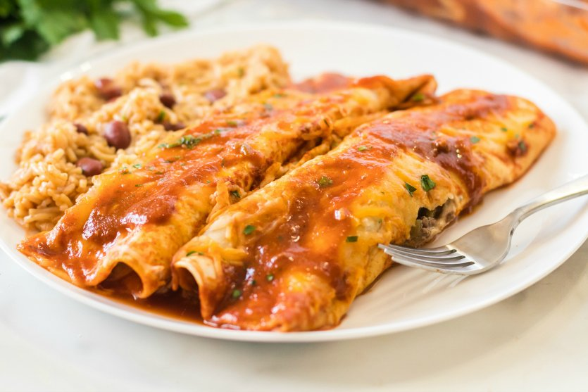 Easy Beef Enchiladas - Served on a white plate with rice - Family Fresh Meals