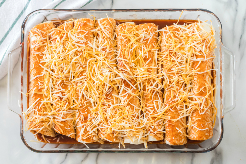 Easy Beef Enchiladas - rolled up tortillas in baking dish and topped with enchilada sauce and shredded cheese - Family Fresh Meals