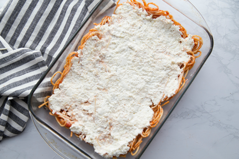 Million Dollar Baked Spaghetti - pasta with cream mixture topping in a baking dish