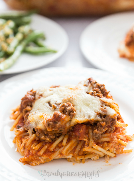 Million Dollar Baked Spaghetti - spaghetti bake served on a white plate and topped with cheese
