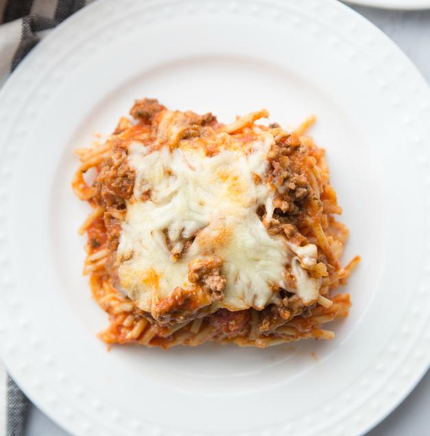 Million Dollar Baked Spaghetti - spaghetti bake served on a white plate