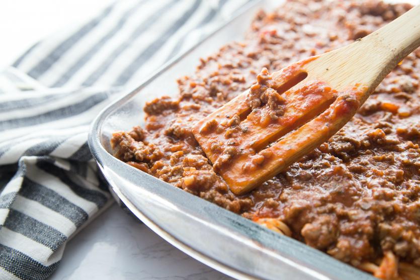 Million Dollar Baked Spaghetti - spreading meat sauce on top of spaghetti bake