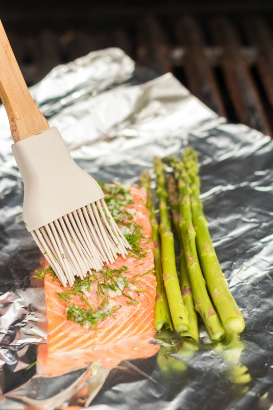 Asparagus Salmon Foil Packets - Brushing dill and garlic on salmon - on the grill