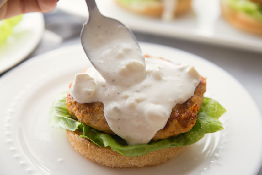 Buffalo Chicken Burgers - spooning blue cheese dressing on top of burger