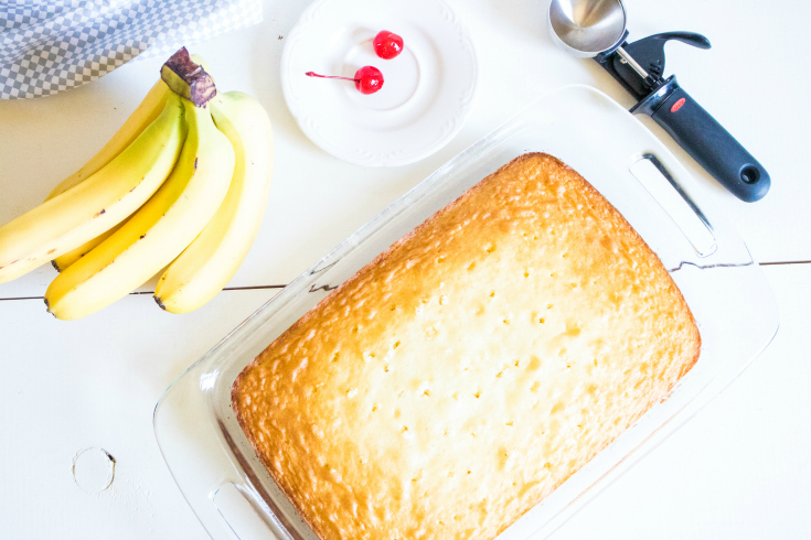 Banana Split Poke Cake - cooked white cake with holes poked in it