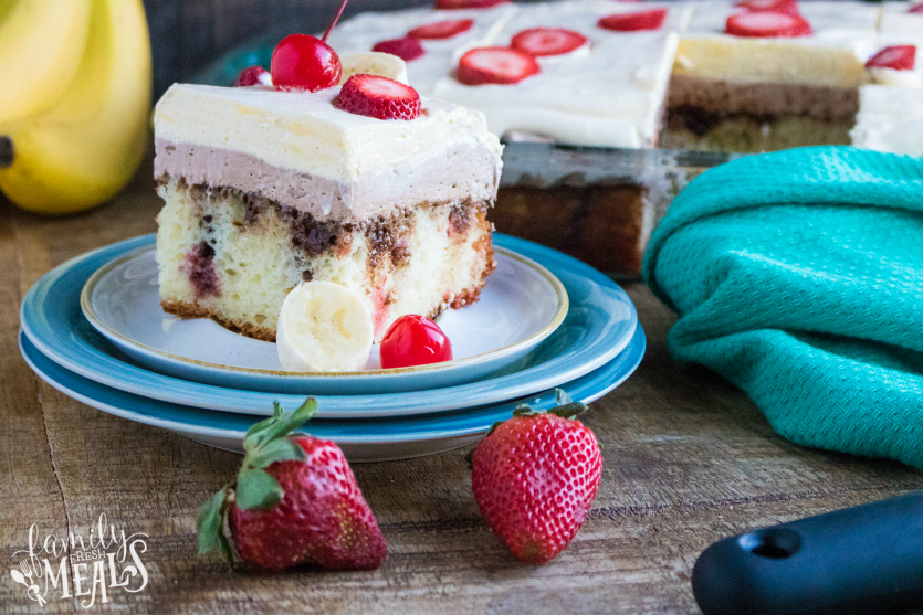 Banana Split Poke Cake - slice of cake served on a plate and topped with banana and strawberry slices