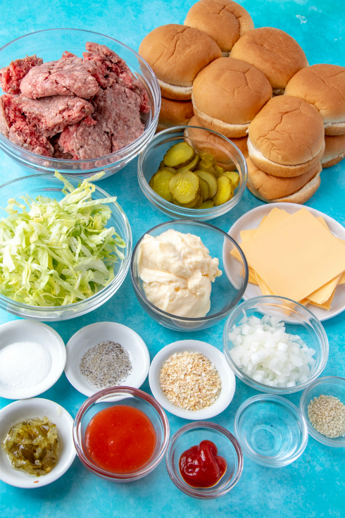 Big Mac Sliders - Ingredients for recipe in small bowls- shredded lettuce, dressing, mayo, seasonings, onion, relish, cheese slices, beef and buns