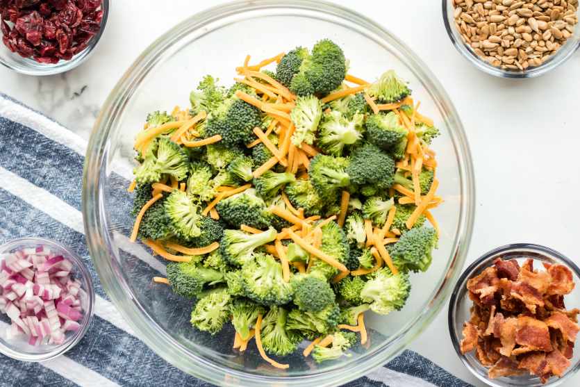 Creamy Broccoli Salad - Ingredients in bowls broccoli, shredded cheese, seeds, bacon, onions and cranberries