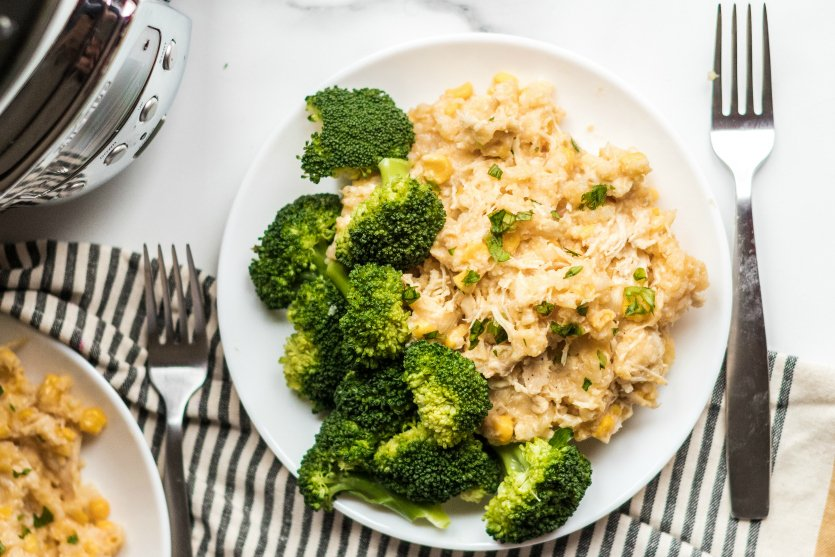Crockpot Creamy Chicken and Rice - Served on a white plate with broccoli