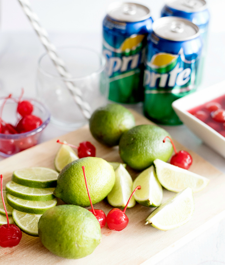 Sonic Cherry Limeade ingredients on cutting board - sprite, limes, cherries