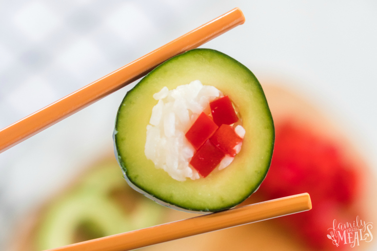 Cucumber Sushi Lunch Box Idea - holding a piece of cucumber sushi with chopsticks